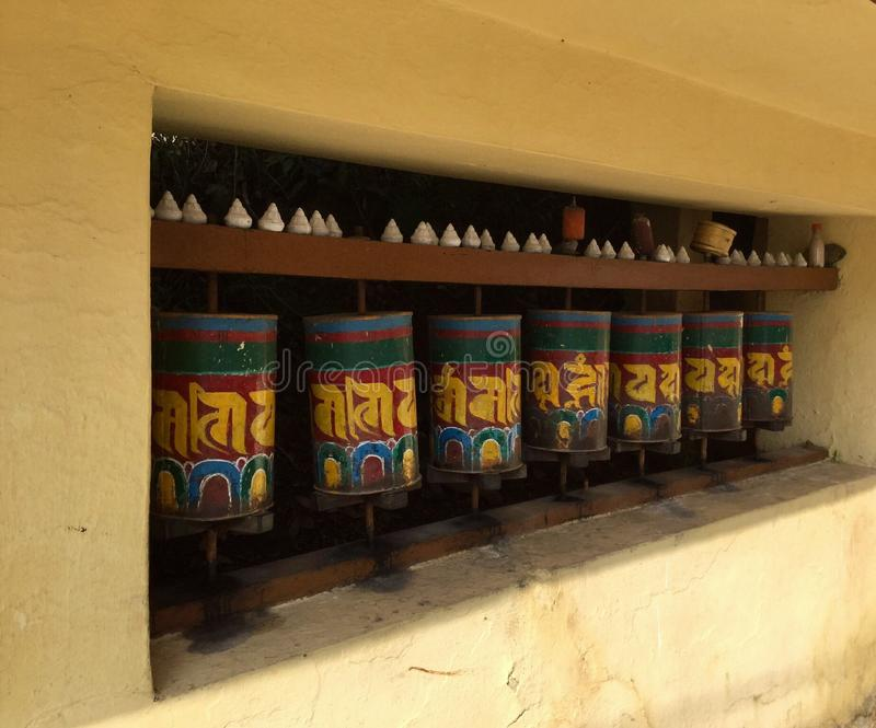 Tibetan Prayer Wheels in the Kora Walk , McLeodgange, Dharamsala, India. A prayer wheel is a cylindrical wheel on a spindle made from metal, wood, stone, leather stock images