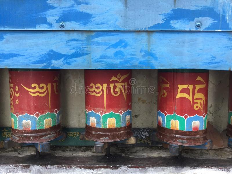 Tibetan Prayer Wheels in the Kora Walk , McLeodgange, Dharamsala, India. A prayer wheel is a cylindrical wheel on a spindle made from metal, wood, stone, leather royalty free stock photos