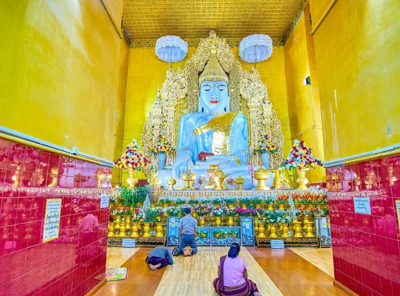The prayers in Kyauktawgyi Buddha Temple, Mandalay, Myanmar. MANDALAY, MYANMAR - FEBRUARY 23, 2018: The prayers pray in the image house of Kyauktawgyi Temple to stock image