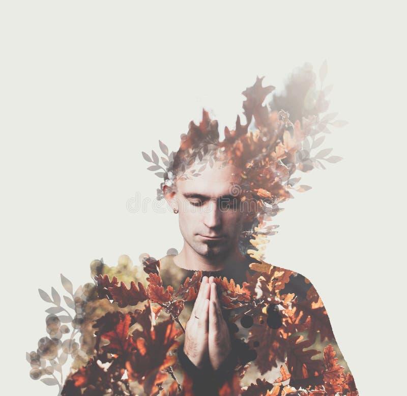 Prayes del hombre de la exposición doble Bosque del otoño alrededor Concepto de paz, apaciguamiento, yoga, mantra, meditación fotos de archivo libres de regalías