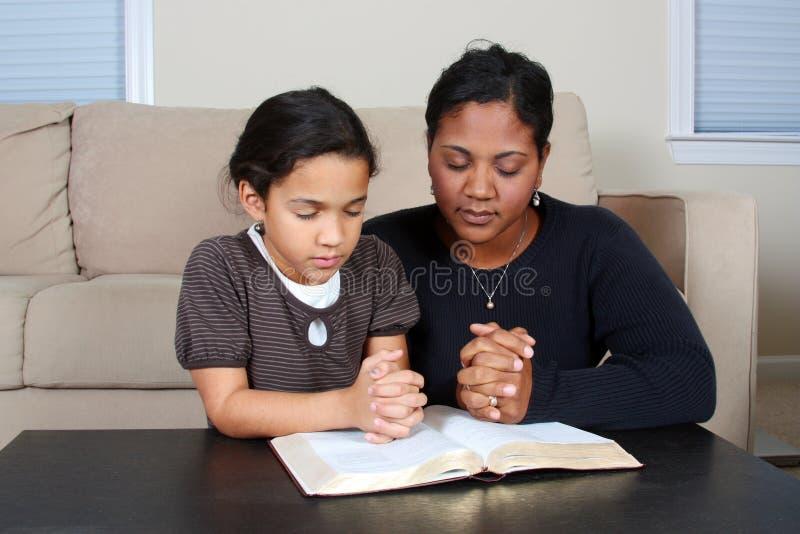 Praying. Minority woman and her daughter praying together