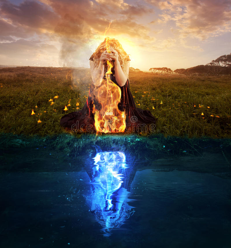 Praying at all times. A woman with a violin on fire and cold reflection stock image