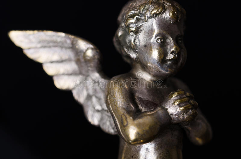 Praying brass angel side view over black stock photo
