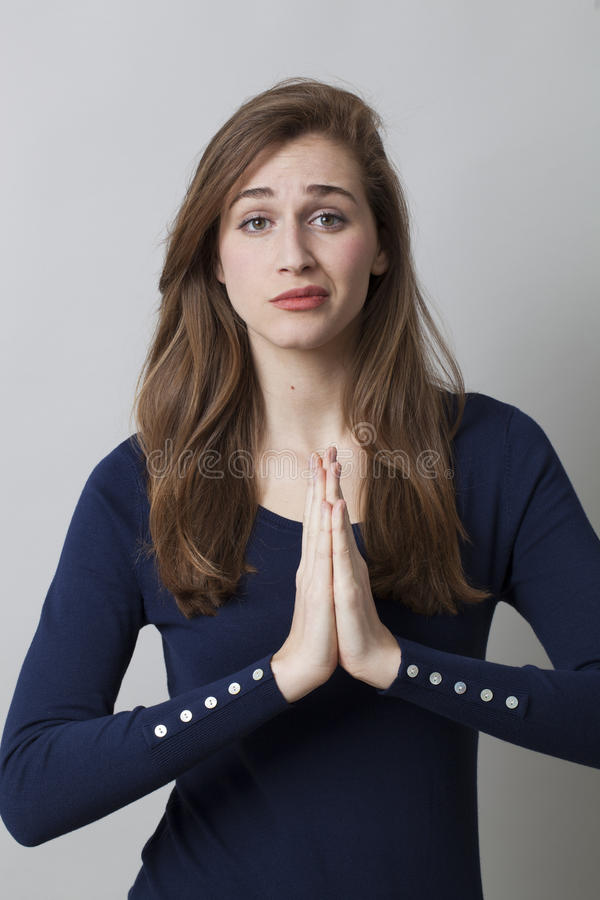 Praying concept, unhappy 20's girl. Praying concept - unhappy beautiful 20s girl trying to pray or seek for zen position with soothing hand gesture, seeking for royalty free stock images