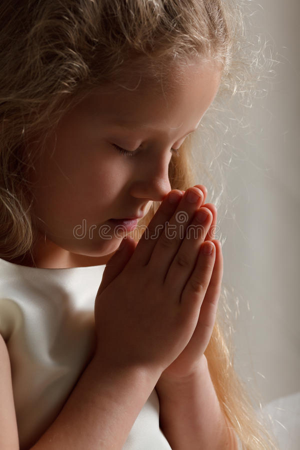 Praying da rapariga imagem de stock