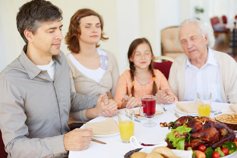 Praying before festive dinner. Family of four praying at festive table on Thanksgiving day, focus on young man royalty free stock photo
