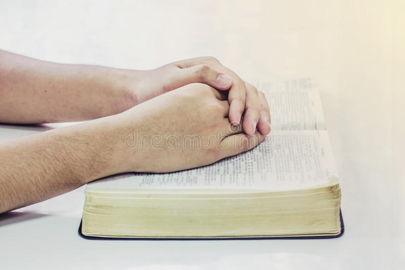 Praying hand of men on open bible book royalty free stock images