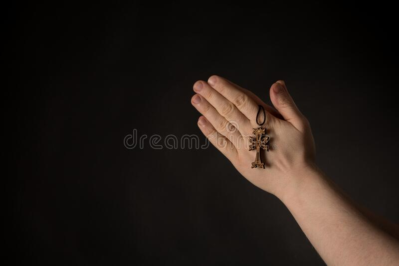 Praying hands with Celtic Cross in hand, asking for help. Copy space stock photos