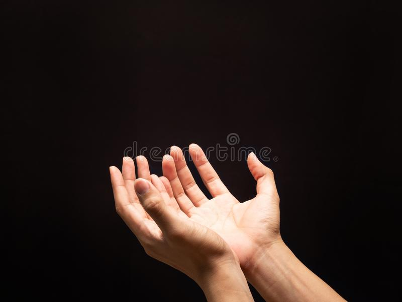 Praying hands in the dark background with faith in religion and belief in God. royalty free stock images