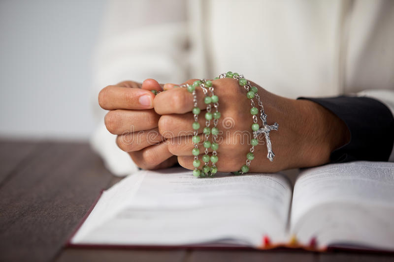 Praying hands of woman with a rosary on bible. Praying hands of woman with a rosary and bible on wooden desk stock images