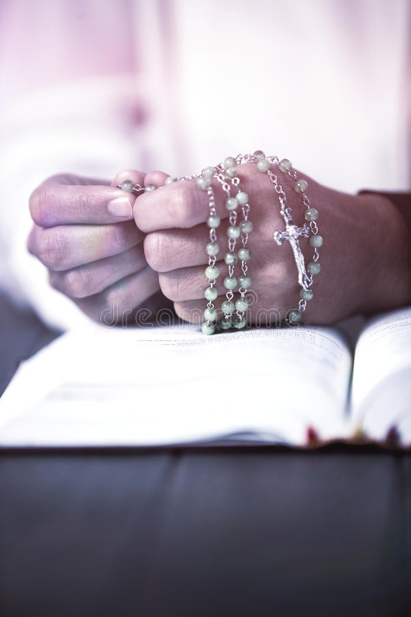 Praying hands of woman with rosary and bible. On wooden desk stock image