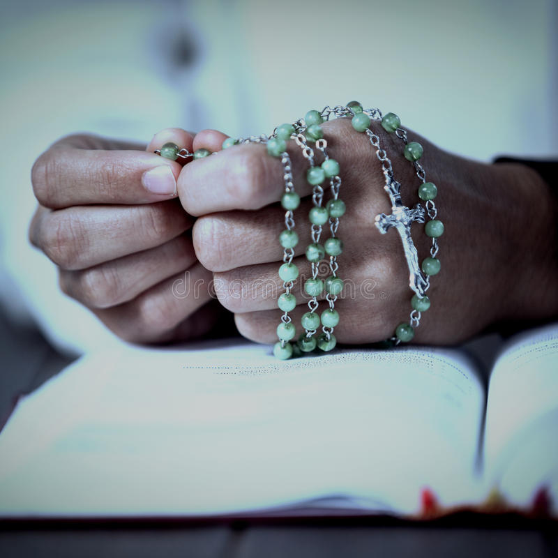Praying hands of woman with rosary and bible. On wooden desk royalty free stock image