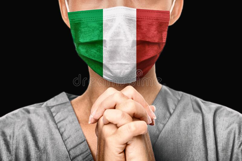 Praying for Italy. Coronavirus pandemic outbreak in Italy. Doctor praying for help. Young woman medical doctor surgeon. Or nurse portrait royalty free stock photo
