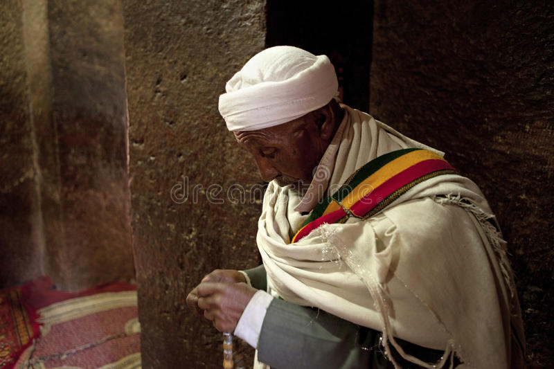 Praying in Lalibela. A priest praying in a monolithic church in Lalibela stock images