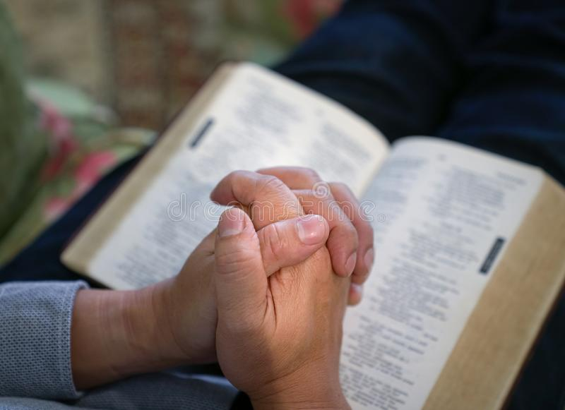 Praying : male hands clasped together on an open bible stock photos