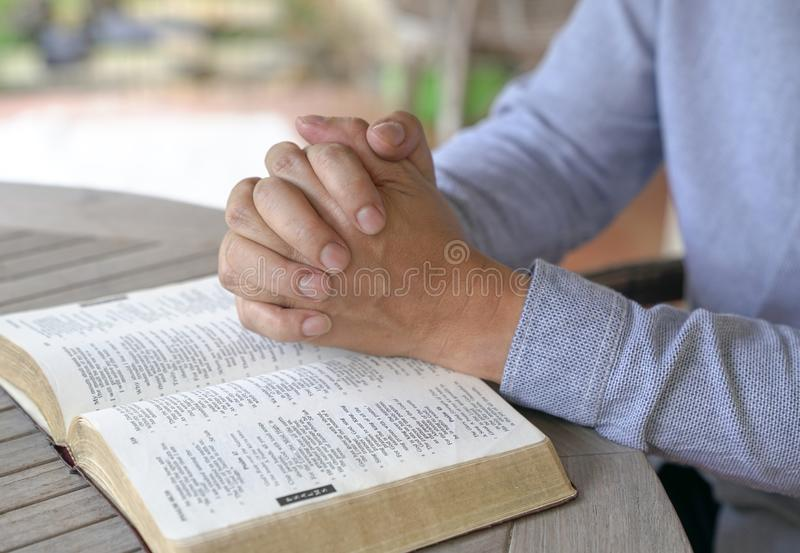 Praying : male hands clasped together on an open bible stock photo