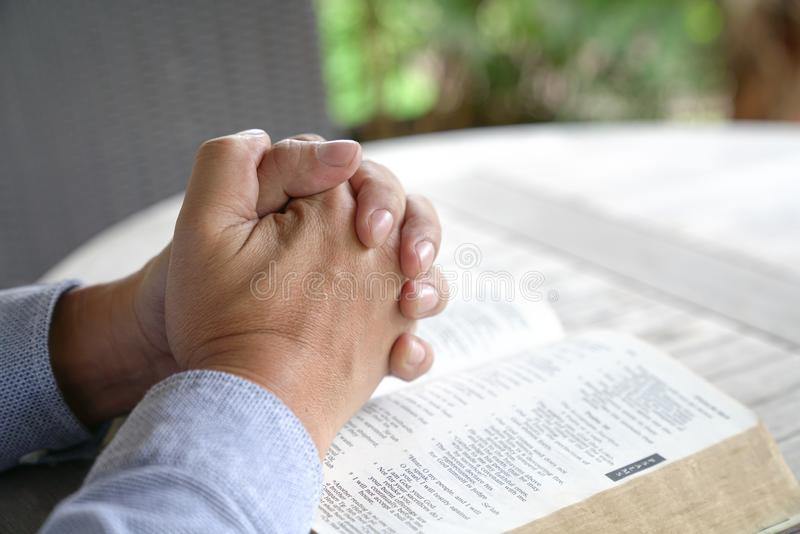Praying : male hands clasped together on an open bible royalty free stock photography