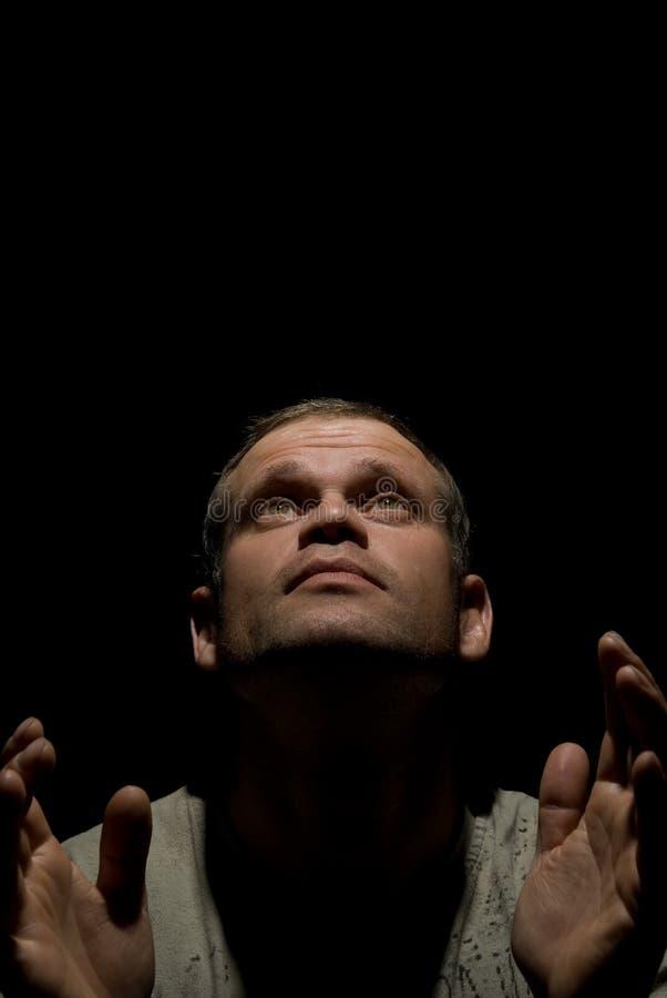 Praying man isolated on black