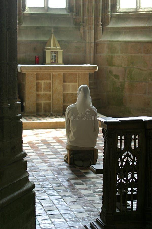 Praying nun in church royalty free stock photography