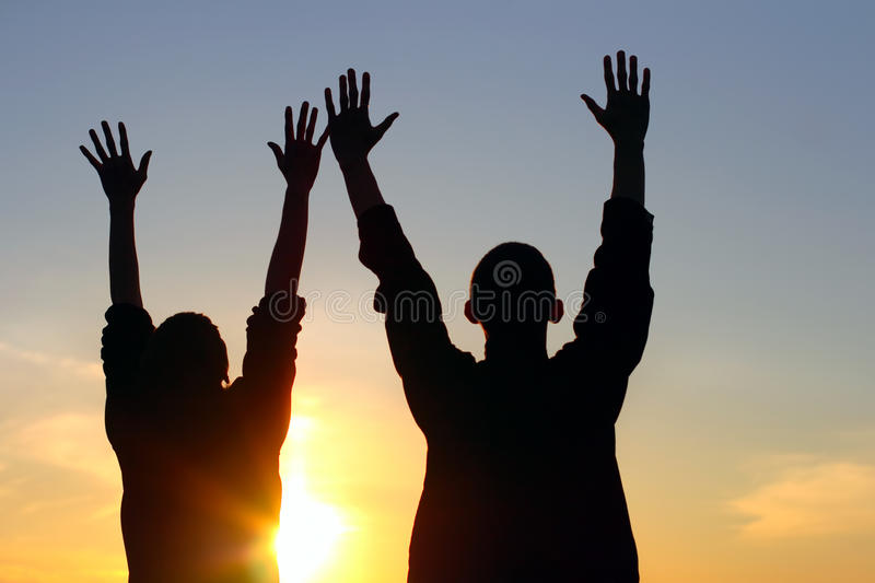 Praying people. Young couple hands up silhouette