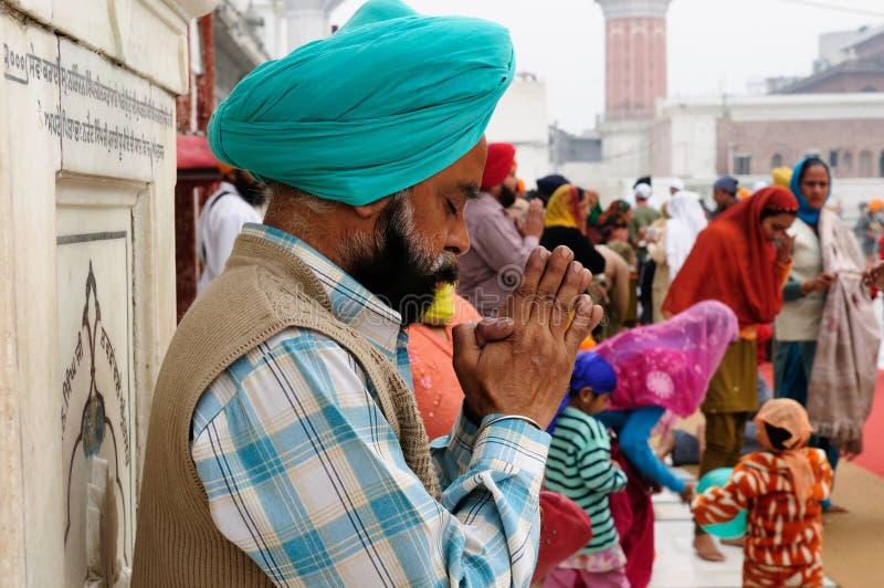 Praying pilgrim in Amritsar. INDIA, AMRITSAR - NOVEMBER 29:Praying pilgrim in the Golden temple (Sri Harimandir Sahib), Amritsar in November 29, 2009 royalty free stock image