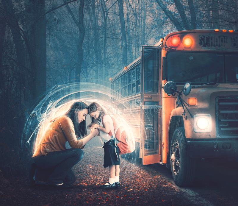 Praying before school starts. A mother and her child in prayer before getting on the school bus royalty free stock images
