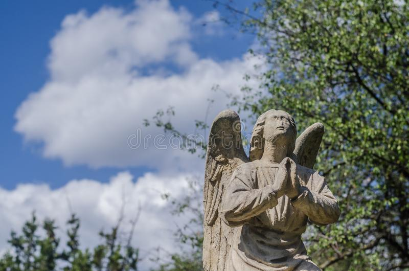 Praying statue and sky. Praying statue looking into the sky cross cemetery religion background jesus christianity faith symbol crucifix god catholic holy easter royalty free stock photo