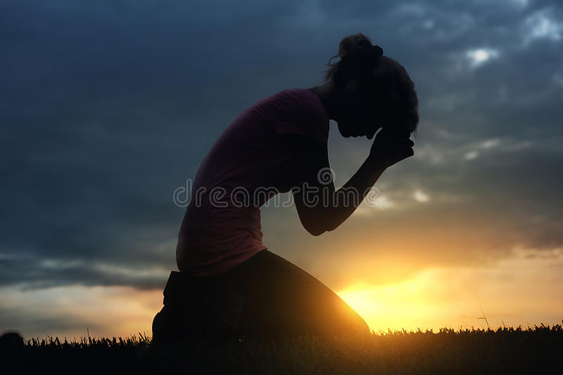 Praying at sunset stock photos