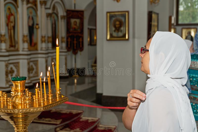Woman praying in Orthodox church. Praying woman standing close to candles in Orthodox church. Belarus, Starobin, June 23, 2018 royalty free stock images