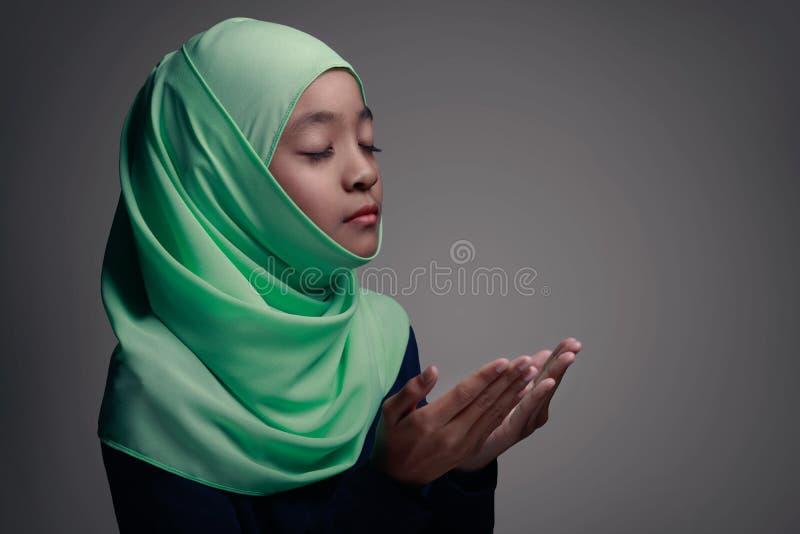 Praying. Young muslim girl praying, Isolated on grey background royalty free stock image