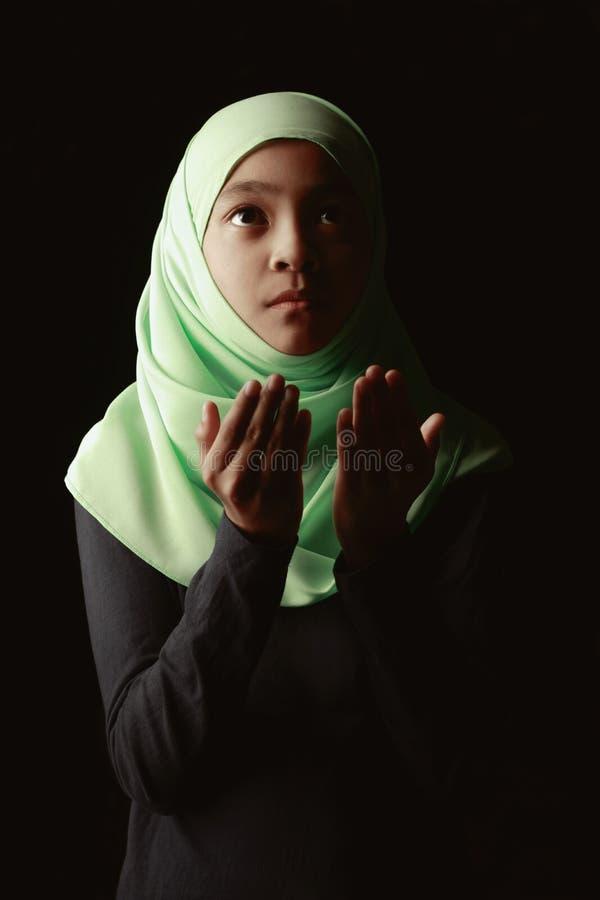 Praying. Young muslim girl praying in mosque royalty free stock image
