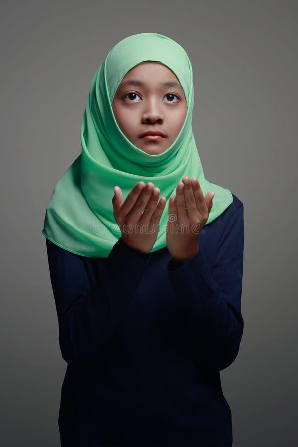 Praying. Young muslim girl praying in mosque stock photo