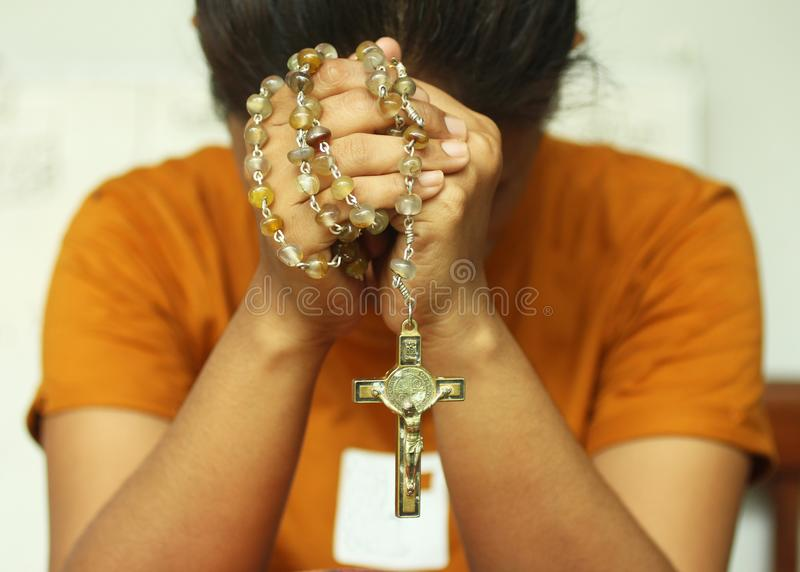 Praying young woman  with bowed head, hands holding rosary beads with Jesus Christ Cross or Crucifix. Christian Catholic religious. Symbol of faith. A religion royalty free stock photo