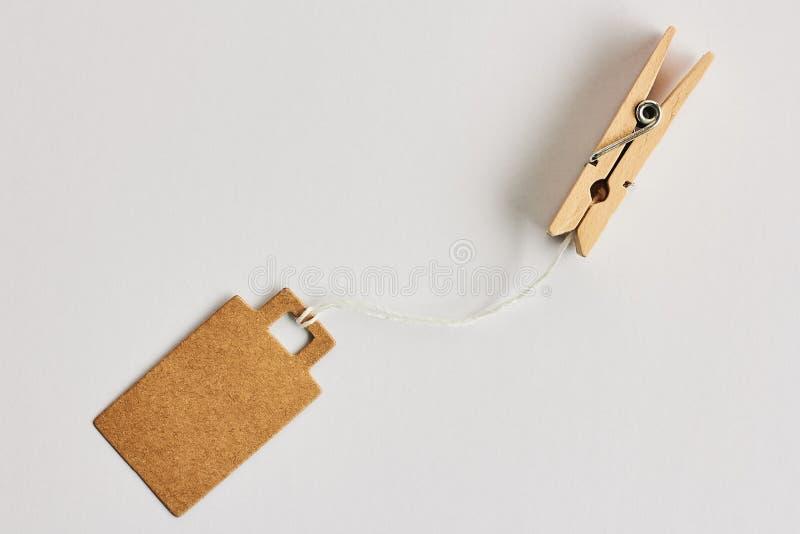 Preço marrom vazio do cartão, etiqueta da venda, etiqueta do presente, etiqueta de endereço que pendura em grampos de madeira da  fotografia de stock