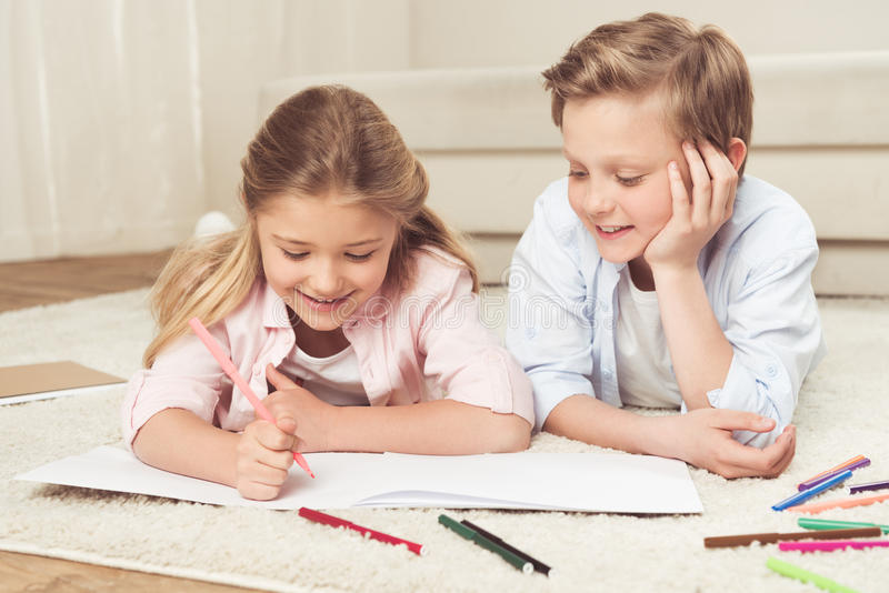 Pre-adolescent kids drawing pictures while lying on the floor at home royalty free stock photography