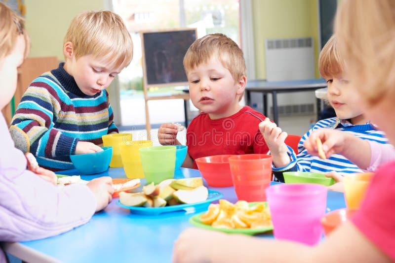 Pre alunos que comem petiscos saudáveis em Breaktime imagens de stock