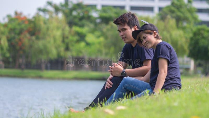 Pre gifta sig skytte: Vännen sitter nära lagun royaltyfria bilder