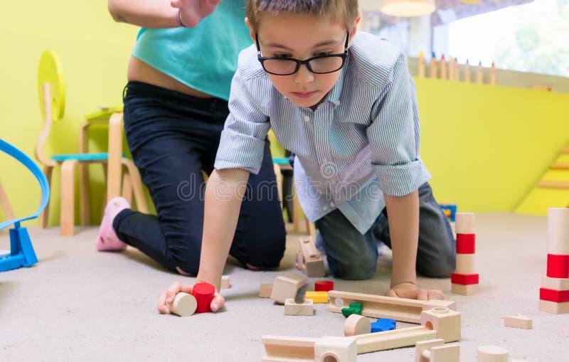 Pre-school jongen die oogglazen dragen terwijl het spelen met houten speelgoed royalty-vrije stock afbeeldingen