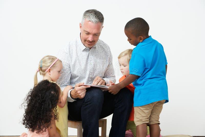 Pre School Teacher Reading Story To Children. Studio Shot stock photography