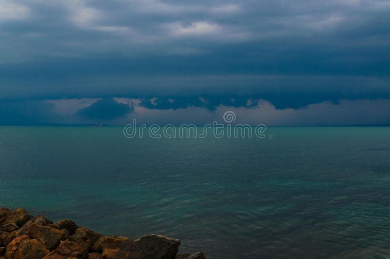 Pre-stormy sky sea smoothness. Seascape with horizon line and dark thunderclouds. View from stone beach with a dark sky. Pre-stormy sky sea smoothness. Seascape stock photos