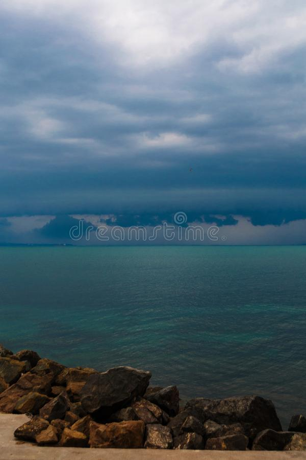 Pre-stormy sky sea smoothness. Seascape with horizon line and dark thunderclouds. View from stone beach with a dark sky. Pre-stormy sky sea smoothness. Seascape royalty free stock images