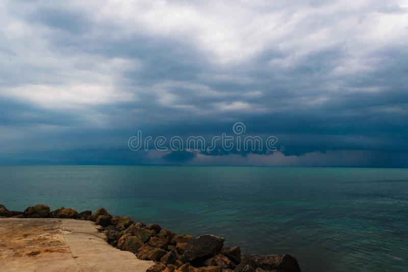 Pre-stormy sky sea smoothness. Seascape with horizon line and dark thunderclouds. View from stone beach with a dark sky. Pre-stormy sky sea smoothness. Seascape royalty free stock photography