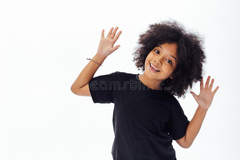 Pre-teen African American kid putting hands up being playful and happy. Isolated over white background royalty free stock images
