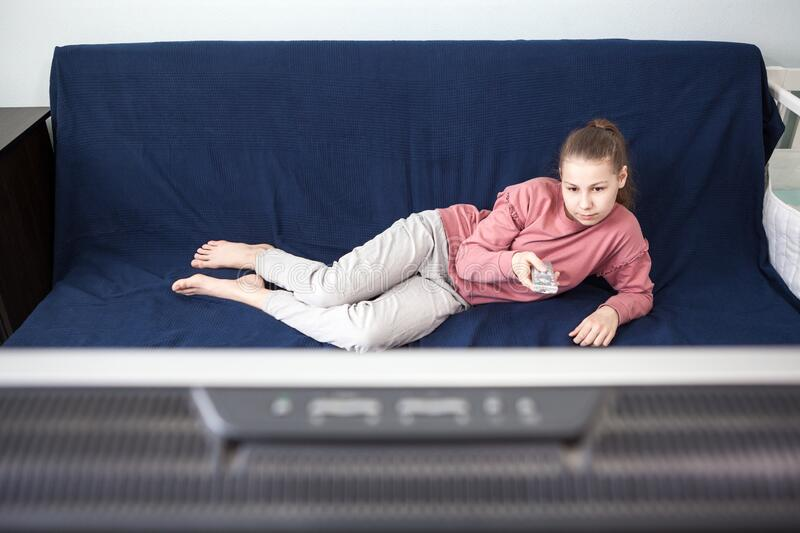 Pre-teen age girl watching television, lying on couch with tv remote control, wide screen is on a foreground. Pre-teen age girl watching television, lying on stock photo