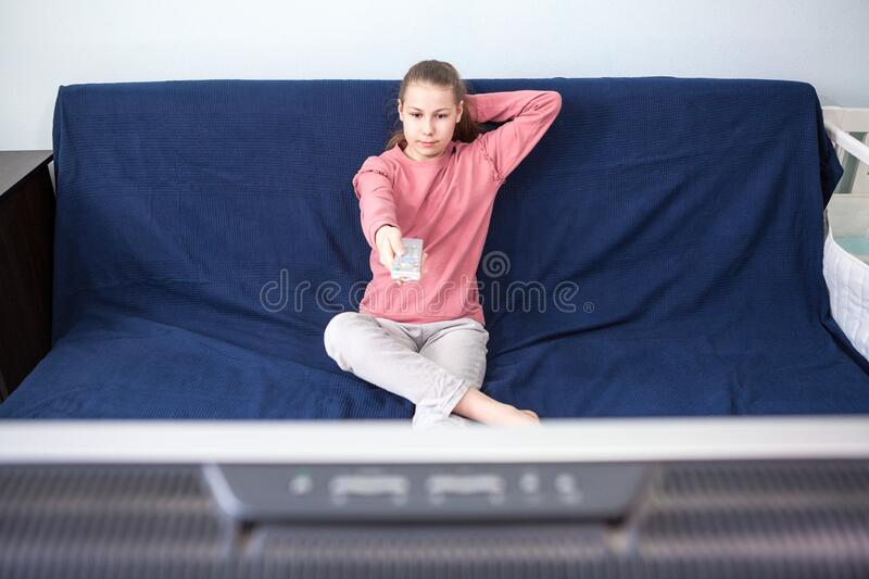 Pre-teen age girl watching television, sits on couch with tv remote control, wide screen is on foreground. Pre-teen age girl watching television, sits on couch stock images