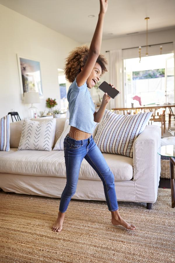Pre-teen African American  girl dancing and singing in the living room at home using her phone as a microphone, side view, full le stock photos