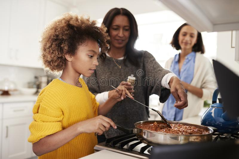 Pre-teen African American  girl standing at the hob in the kitchen preparing food with her grandmother and mother, close up, selec stock photos