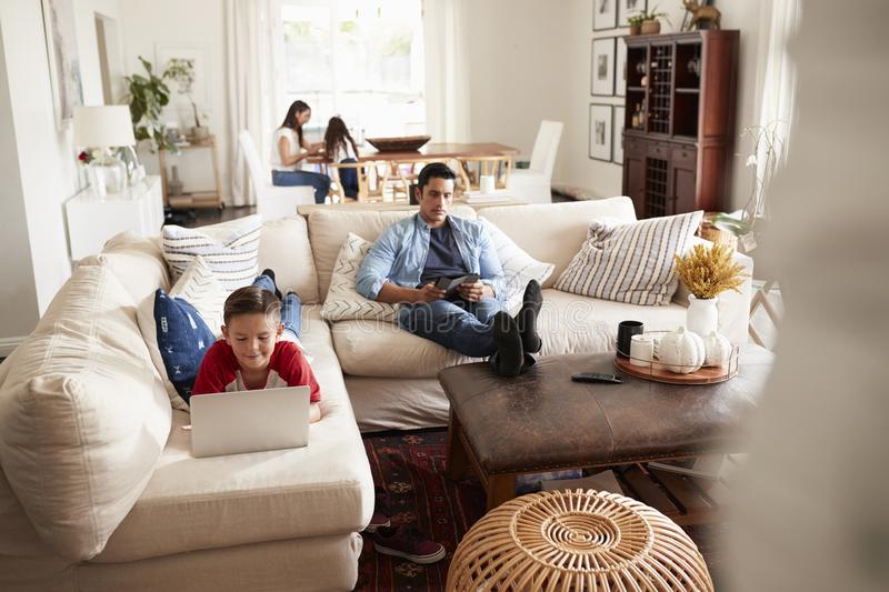 Pre-teen boy lying on sofa using laptop, dad sitting with a tablet, mum and sister in the background royalty free stock images