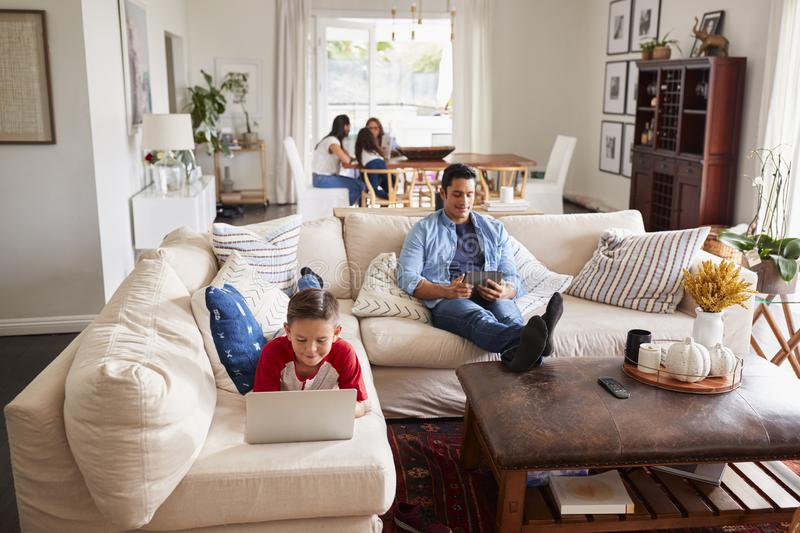 Pre-teen boy lying on sofa using laptop, dad using tablet, mum, sister and grandma in the background royalty free stock photography