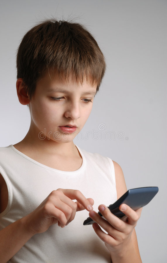 Pre-teen boy with mobile phone on light background stock photo